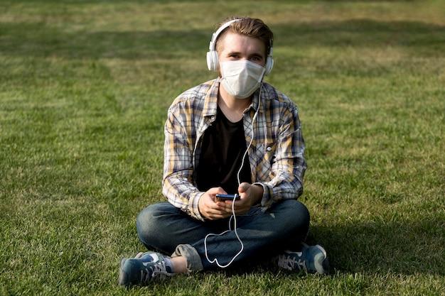 Hombre joven con estilo con mascarilla escuchando música