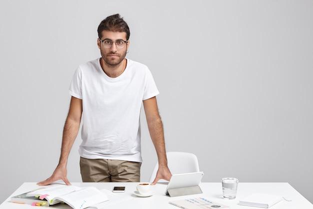 Hombre joven con estilo de pie cerca del escritorio