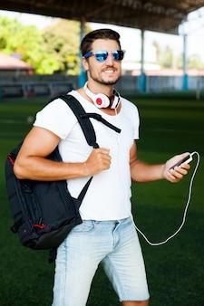 Hombre joven con estilo posando en un campo de fútbol, escuchar música. auriculares en los hombros, sosteniendo al jugador en la mano, gafas de sol en la cara
