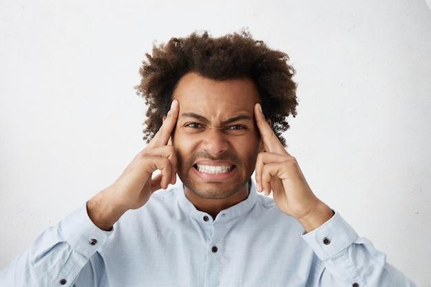 Hombre joven estresado apretando las sienes y apretando los dientes