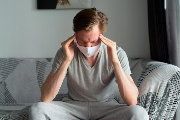 Hombre joven estresado con máscara que tiene dolor de cabeza en casa en cuarentena