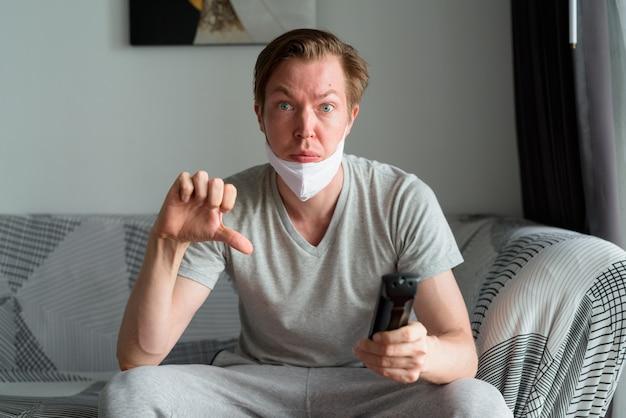 Hombre joven estresado con máscara viendo la televisión y dando pulgares hacia abajo en casa en cuarentena