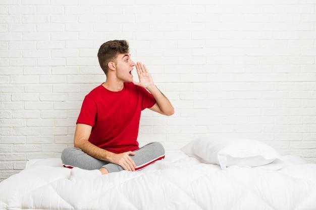 Hombre joven estudiante adolescente en la cama gritando y sosteniendo la palma cerca de la boca abierta.