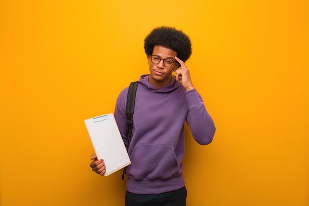 Hombre joven estudiante afroamericano sosteniendo un portapapeles pensando en una idea