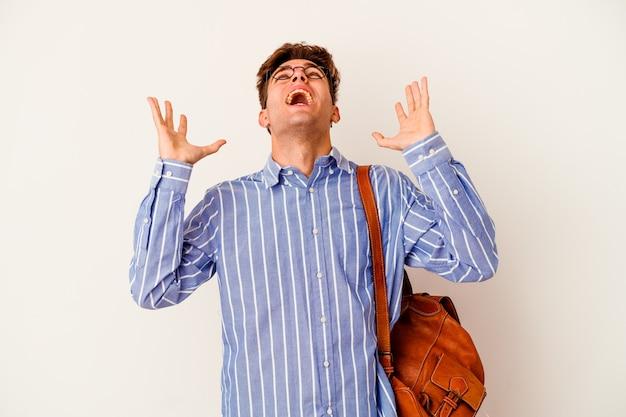 Hombre joven estudiante aislado en la pared blanca gritando al cielo, mirando hacia arriba, frustrado