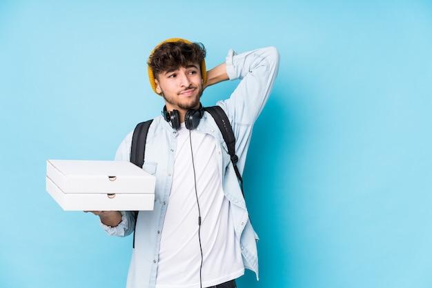 Hombre joven estudiante árabe sosteniendo pizzas aisladas tocando la parte posterior de la cabeza, pensando y haciendo una elección.