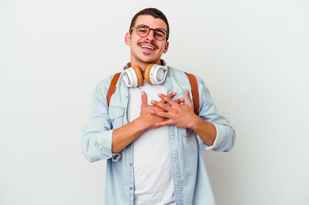 El hombre joven estudiante caucásico escuchando música aislada en blanco tiene una expresión amistosa, presionando la palma contra el pecho. concepto de amor.