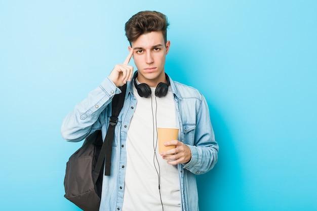 Hombre joven estudiante caucásico sosteniendo un café para llevar apuntando su sien con el dedo, pensando, centrado en una tarea.