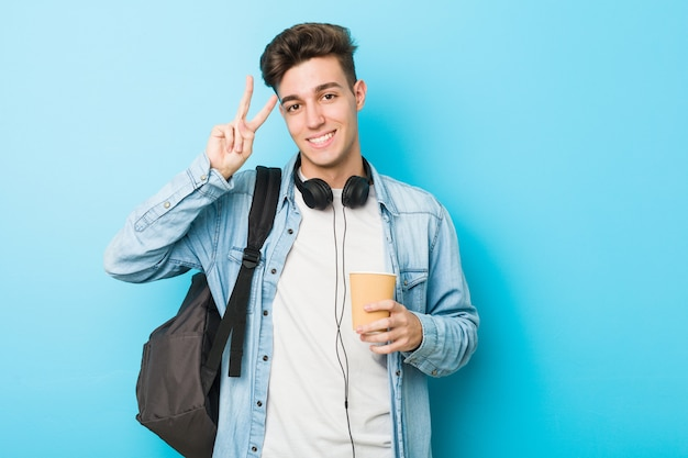 Hombre joven estudiante caucásico sosteniendo un café para llevar mostrando el signo de la victoria y sonriendo ampliamente.