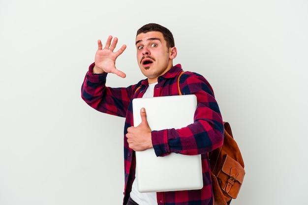 Hombre joven estudiante caucásico sosteniendo un portátil aislado en la pared blanca conmocionado debido a un peligro inminente