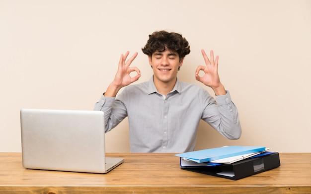 Hombre joven del estudiante con una computadora portátil en actitud del zen