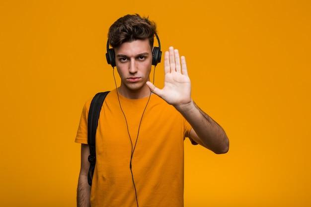 Hombre joven estudiante fresco escuchando música con auriculares apuntando su sien con el dedo, pensando, centrado en una tarea.