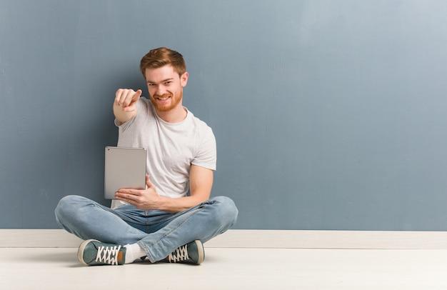 Hombre joven estudiante pelirroja sentada en el suelo alegre y sonriente apuntando al frente. él está sosteniendo una tableta.