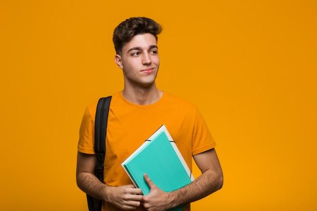 Hombre joven del estudiante que sostiene los libros que muerden las uñas, nervioso y muy ansioso.