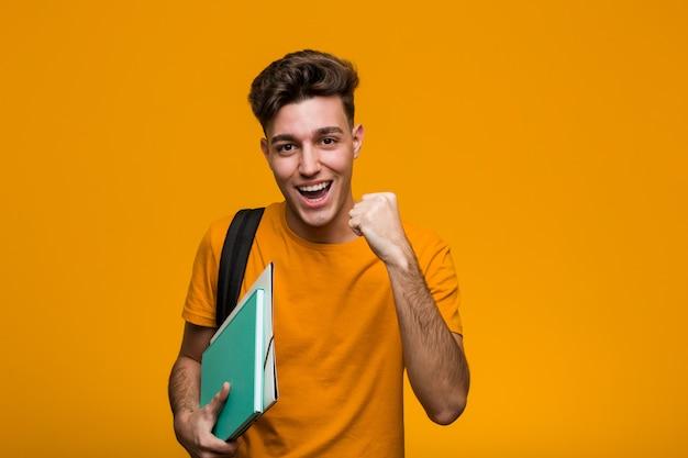 Hombre joven estudiante sosteniendo libros celebrando una victoria