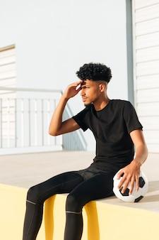 Hombre joven étnico que se sienta con el balón de fútbol en luz del sol