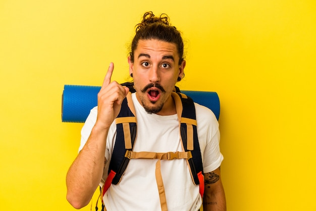 Hombre joven excursionista caucásico con pelo largo aislado sobre fondo amarillo con una idea, concepto de inspiración.