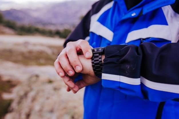 Hombre joven excursionista comprobar reloj inteligente en la cima de la montaña. día nublado