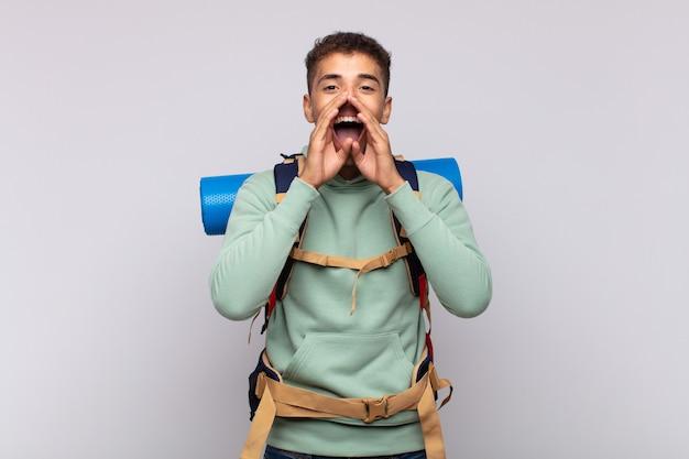 Hombre joven excursionista que se siente feliz, emocionado y positivo, dando un gran grito con las manos al lado de la boca