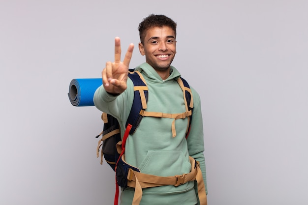 Hombre joven excursionista sonriendo y mirando feliz, despreocupado y positivo, gesticulando victoria o paz con una mano