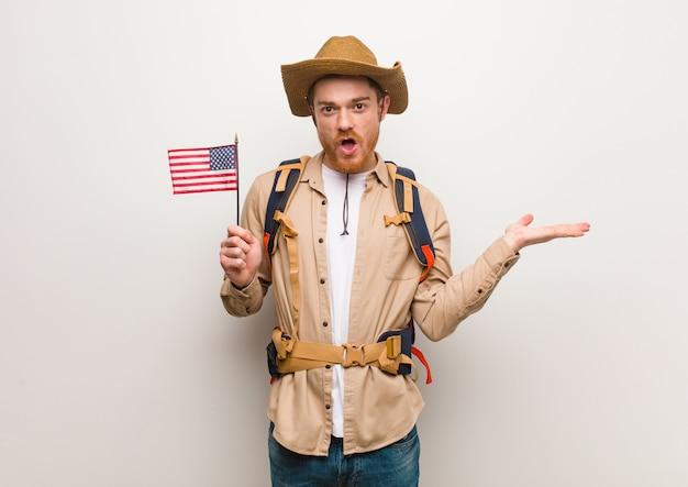 Hombre joven explorador pelirroja sosteniendo algo en la mano de la palma. sosteniendo una bandera de estados unidos.
