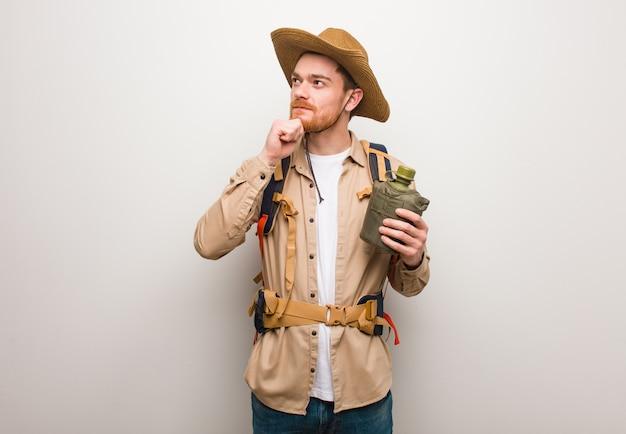 Hombre joven explorador pelirrojo dudando y confundido. él está sosteniendo una cantimplora.