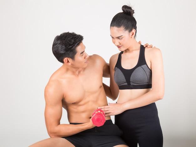 Hombre joven feliz de la aptitud y su novia en tiempo del entrenamiento. fitness y estilo de vida saludable concepto. foto de estudio con fondo blanco.