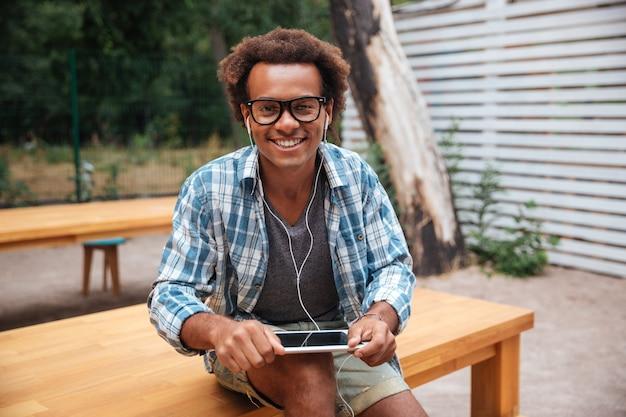 Hombre joven feliz en gafas y auriculares con tableta en el parque