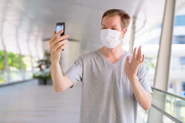 Hombre joven feliz con máscara para protegerse del brote de virus corona videollamadas en la ciudad al aire libre