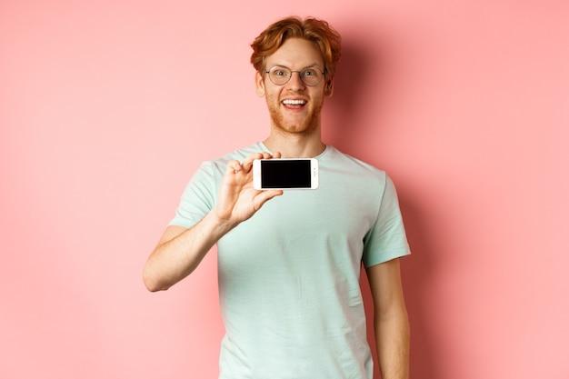 Hombre joven feliz con el pelo rojo que muestra la pantalla del teléfono inteligente