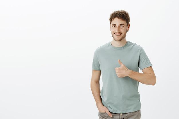 Hombre joven feliz positivo en aretes, sonriendo ampliamente sosteniendo la mano en el bolsillo y mostrando los pulgares para arriba