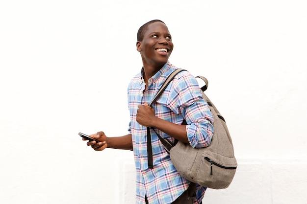 Hombre joven feliz que camina con el bolso y el teléfono móvil contra el fondo blanco