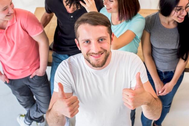 Hombre joven feliz que se coloca con los amigos que muestran el gesto del thumbup que mira la cámara