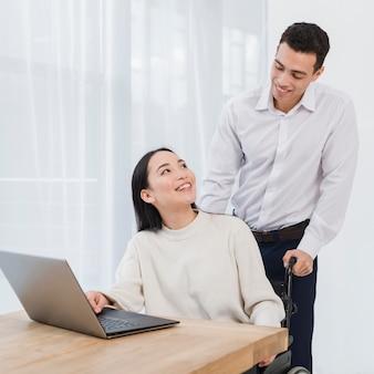 Hombre joven feliz que se coloca detrás de la mujer asiática que usa el ordenador portátil en la tabla de madera