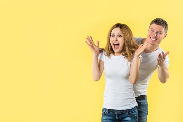 Hombre joven feliz que se coloca detrás de la mujer joven emocionada que parece sorprendida