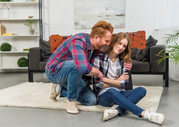 Hombre joven feliz que consuela a su novia triste en casa