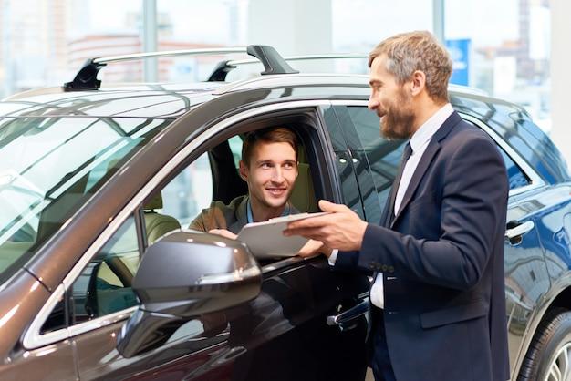 Hombre joven feliz que elige el coche nuevo