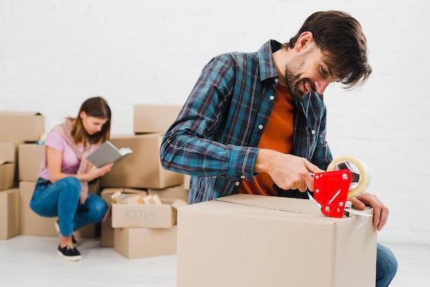 Hombre joven feliz que embala la caja de cartón y su esposa en el fondo
