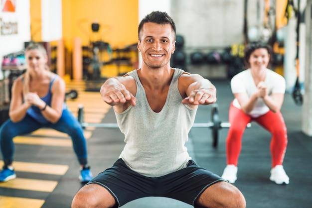 Hombre joven feliz que hace ejercicio del calentamiento en gimnasio