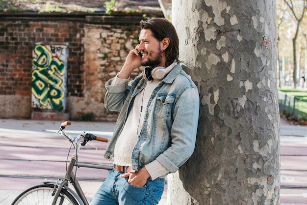 Hombre joven feliz que se inclina en el tronco de árbol que habla sobre el teléfono móvil con su mano en bolsillo