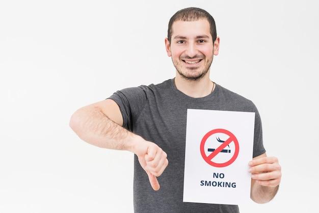 Hombre joven feliz que lleva a cabo la muestra de no fumadores que muestra el pulgar abajo aislado en el contexto blanco