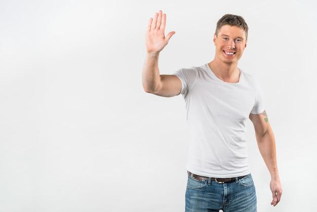 Hombre joven feliz que muestra sus manos contra el fondo blanco