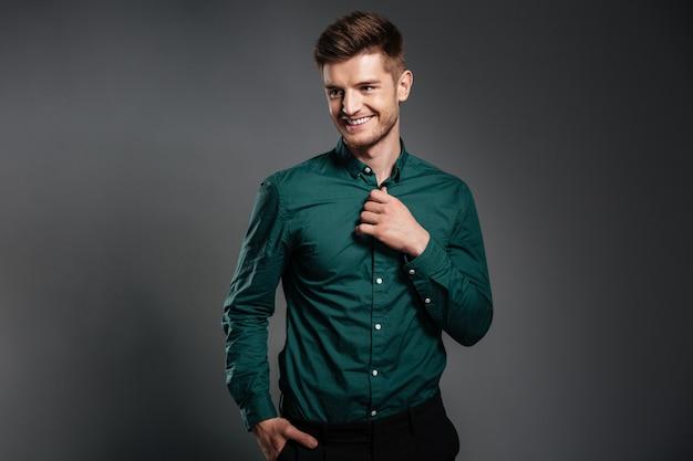 Hombre joven feliz que presenta aislado sobre gris