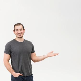 Hombre joven feliz que presenta sobre fondo blanco