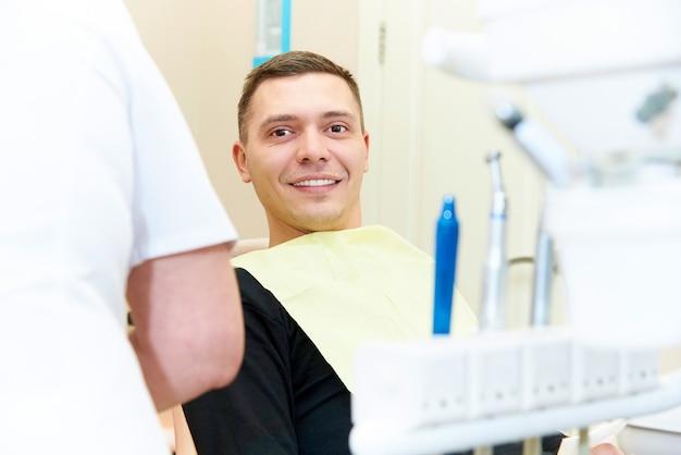 Hombre joven feliz que se sienta en silla dental