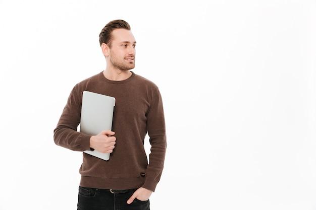 Hombre joven feliz que sostiene el ordenador portátil.