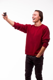 Hombre joven feliz que toma la fotografía del autorretrato a través del teléfono inteligente aislado sobre la pared blanca
