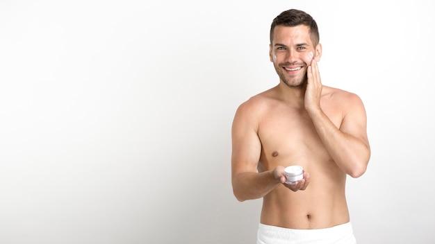 Hombre joven feliz que usa la crema en su cara contra la pared blanca