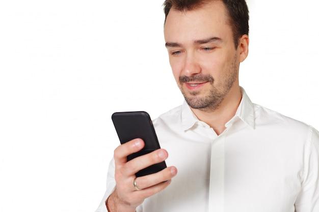 Hombre joven feliz que usa el teléfono móvil