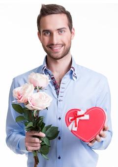 Hombre joven feliz con rosas rosadas y un regalo - aislado en blanco.